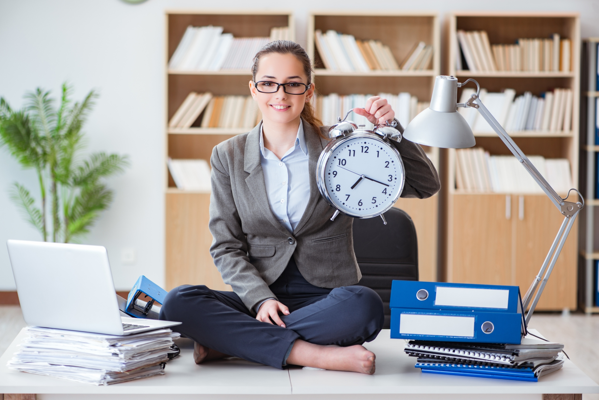 Business woman holding up a large clock
