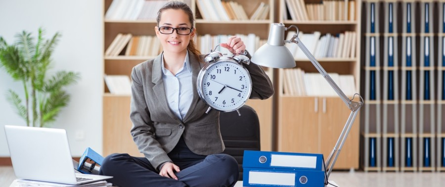Business woman in a an office, holding a clock.