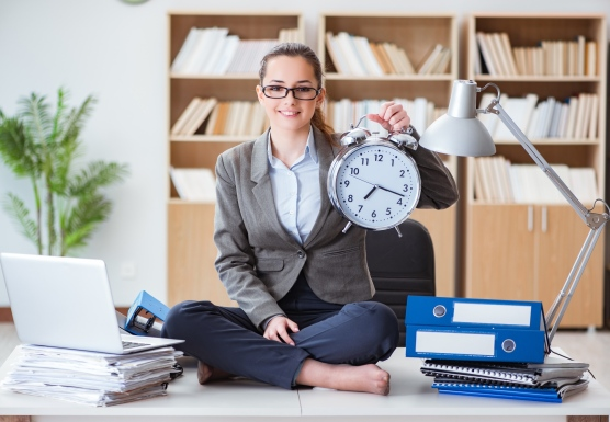 Business woman in an office, holding a clock
